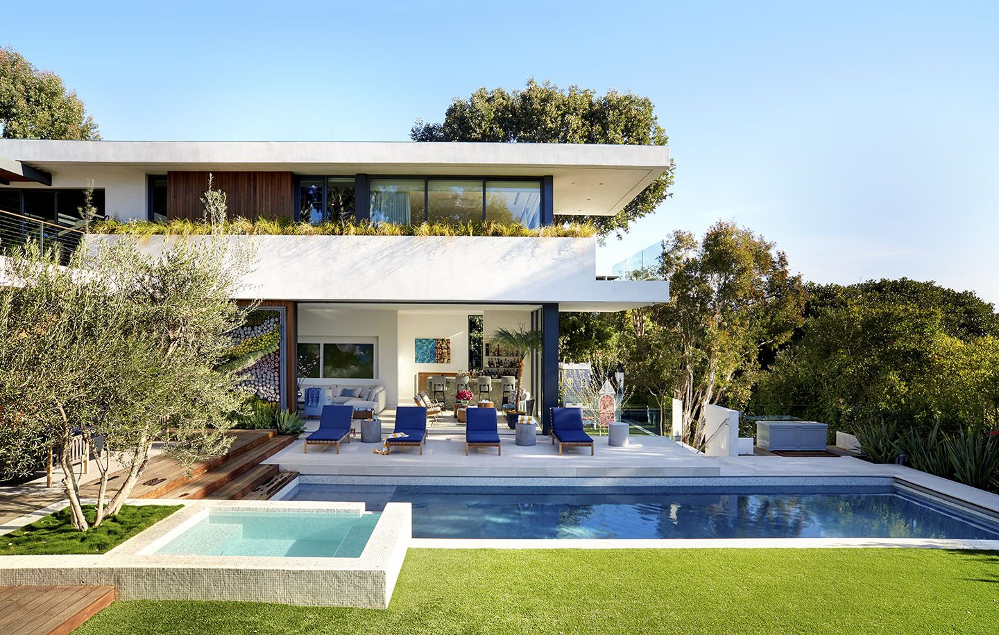 Adam Hunter designed modern home with swimming pool and blue lounge chairs.